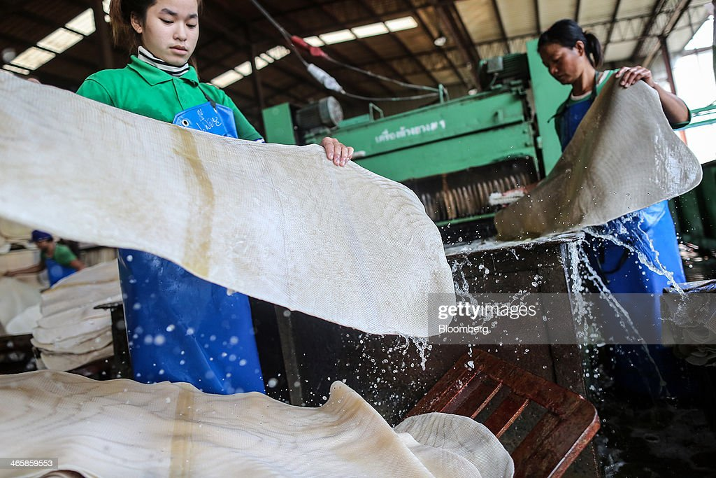 Workers handle rubber sheets as they pass through a rubber sheet washing machine at the Thai Hua Rubber Pcl factory in Samnuktong, Rayong province, Thailand, on Wednesday, Jan. 29, 2014. Rubber production in Thailand, the world's largest exporter, may decline as growers from the main producing regions join protests seeking to overthrow the government, according to Von Bundit Co. Photographer: Dario Pignatelli/Bloomberg via Getty Images