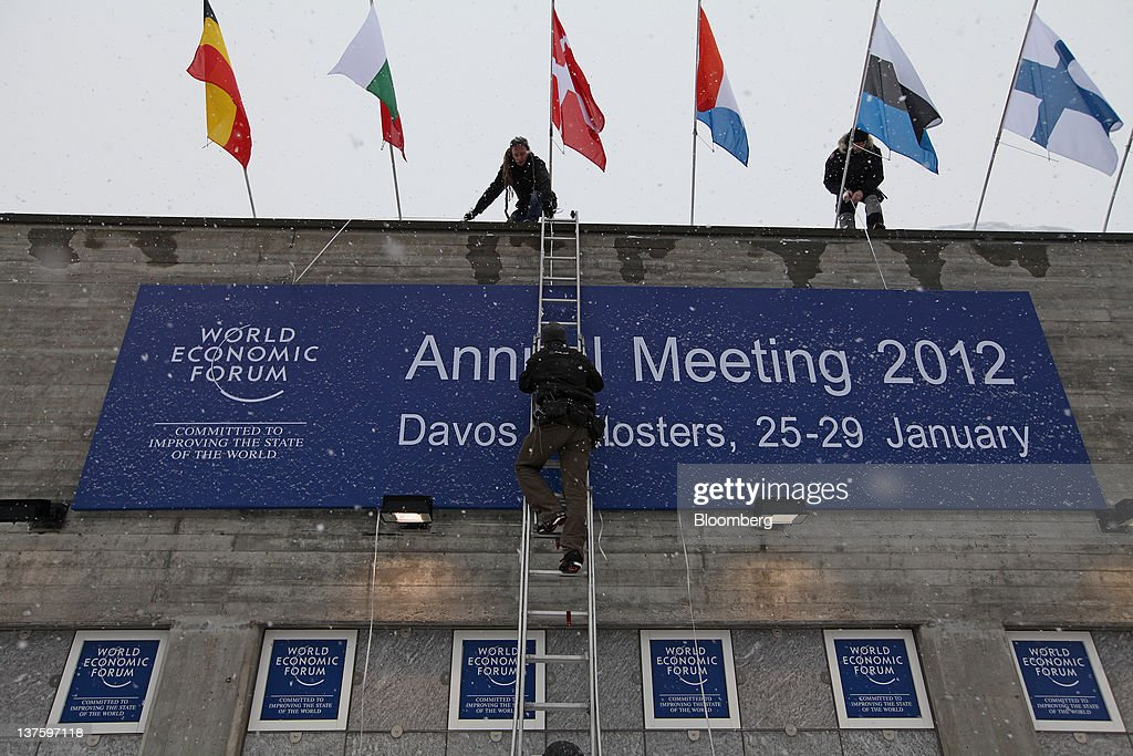 Workers hang a large sign for the World Economic Forum's (WEF) 2012 annual meeting, outside of the Congress Centre in the town of Davos, Switzerland, on Monday, Jan. 23, 2012. German Chancellor Angela Merkel will open this week's World Economic Forum in Davos, Switzerland, which will be attended by policy makers and business leaders including U.S. Treasury Secretary Timothy F. Geithner. Photographer: Chris Ratcliffe/Bloomberg via Getty Images