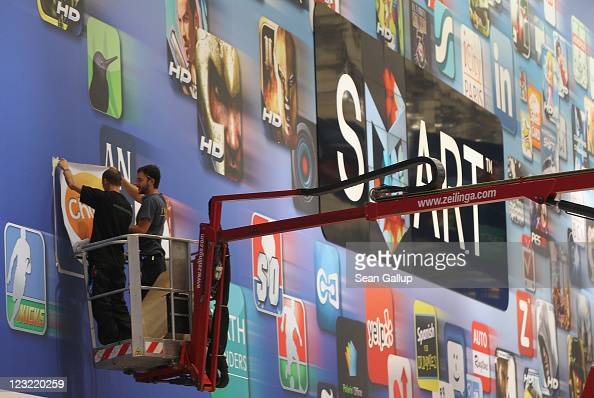 Workers hang a sticker on a giant mural advertising Samsung's Smart TV at the Samsung hall at the IFA 2011 consumer electonics and appliances trade...