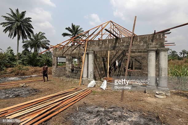 Workers hang around an unfinished new house developed with compensation money paid to the local community by the Royal Dutch Shell Plc oil company as...