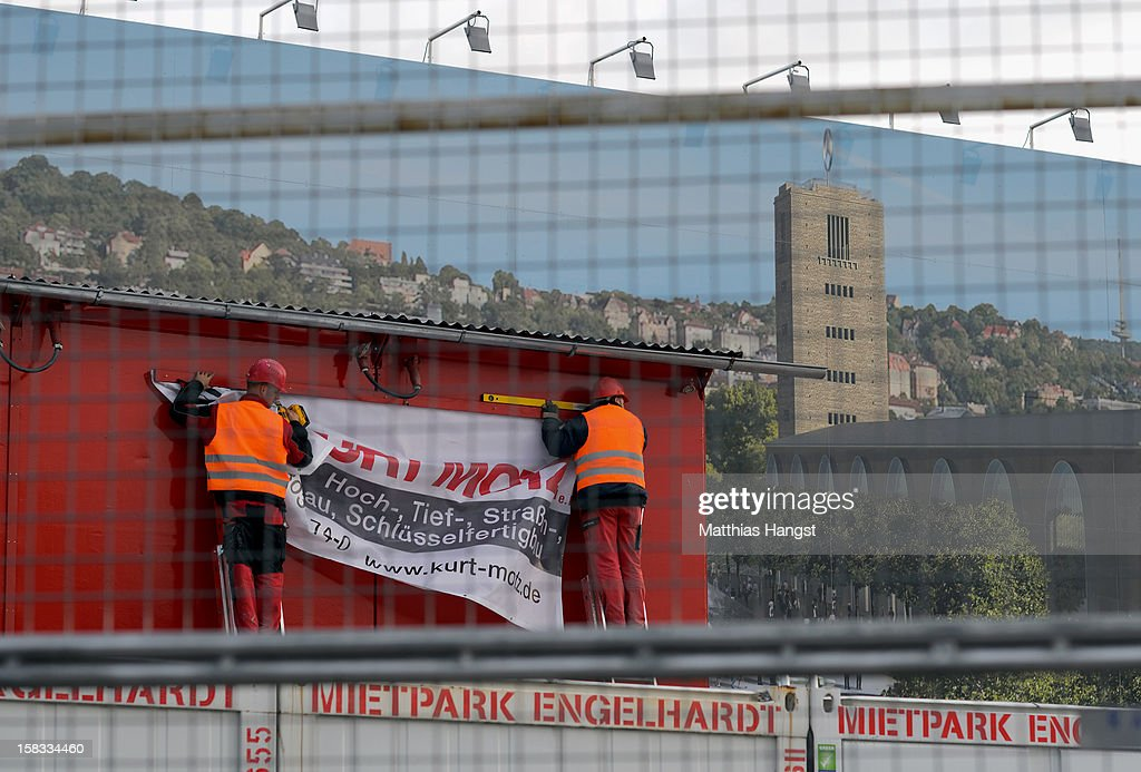 Workers hang-up a placard at the construction site of the Stuttgart 21 railway station on December 13, 2012 in Stuttgart, Germany. German state rail carrier Deutsche Bahn, which is carrying out the massive project, announced yesterday that final costs will be EUR 1.1 billion more than previously expected, bringing the total cost to EUR 5.6 billion. The project will replace the current overground, terminal station with a more efficient underground one. Critics have decried the project as too expensive and too environmentally risky.