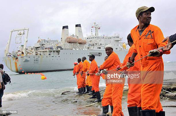 Workers haul part of a fibre optic cable onto the shore at the Kenyan port town of Mombasa on June 12 2009 An undersea fibre optic cable bringing...