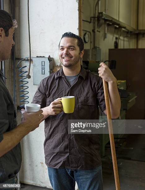 Workers having coffee together in warehouse
