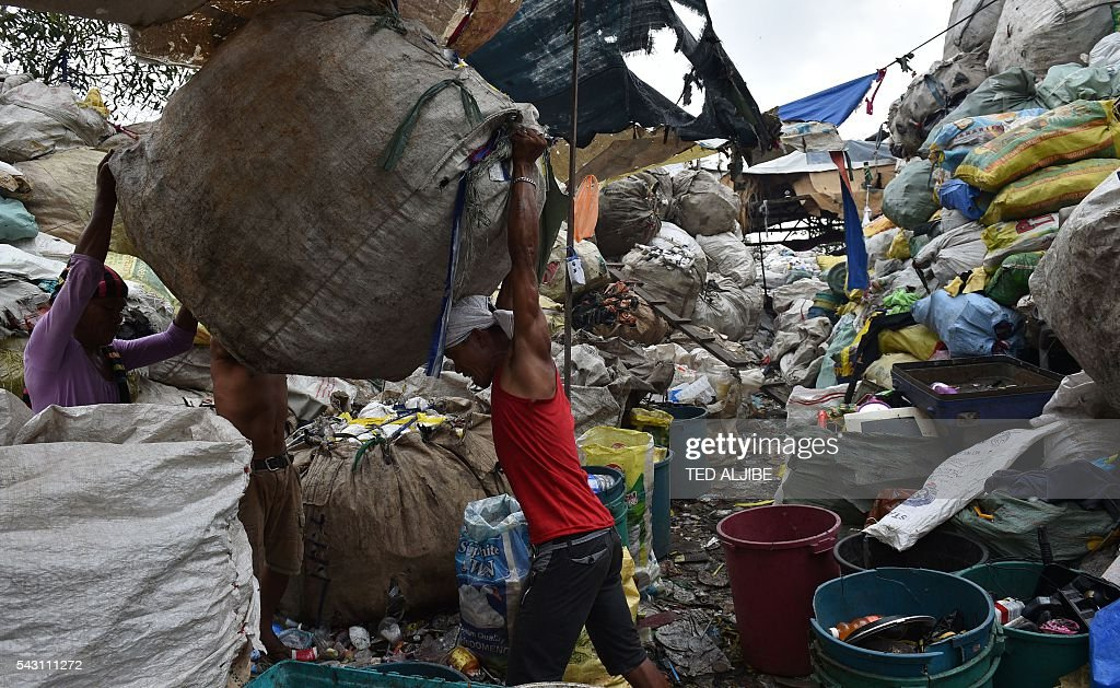 Workers help a colleague load a bale of collected recyclable materials at a junk shop near the former dumpsite and landfill named 'Smokey Mountain' in Manila on June 26, 2016. Incoming Philippine president Rodrigo Duterte pledged on May 26 to spread economic activity beyond the overpopulated capital of Manila, calling it a 'dead' city overrun by shantytowns. / AFP / TED