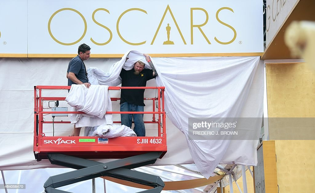 Workers help with decorations above the red carpet as final preparations take place on February 21 2015 one day before the 87th annual Academy Awards...