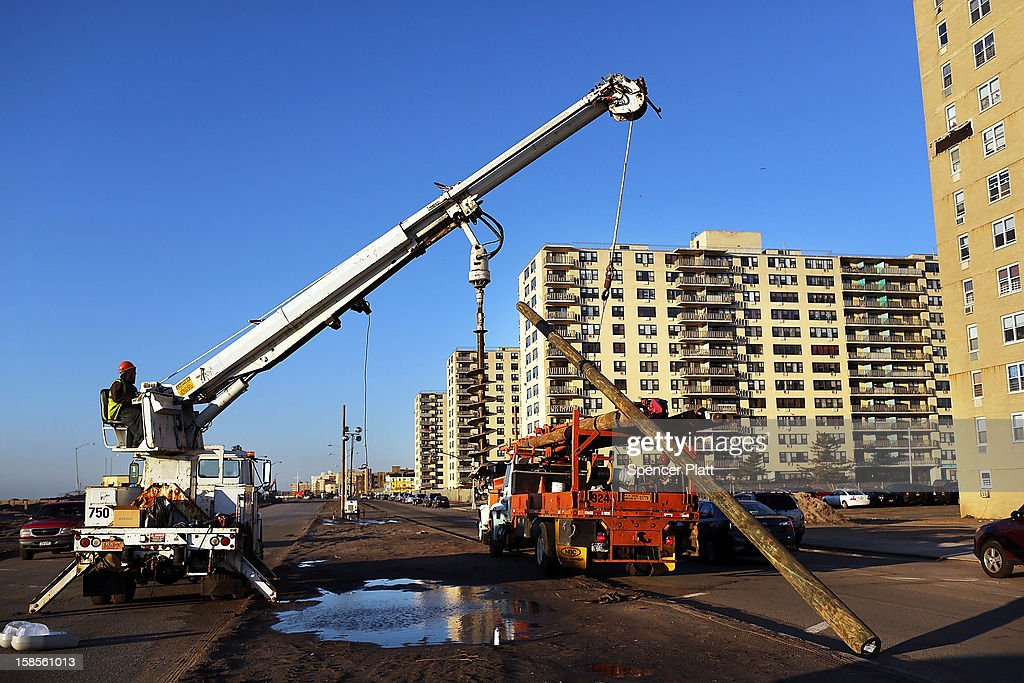 Workers helps install a new street lamp after the old ones were destroyed in flooding on November 19, 2012 in the Queens borough of New York City. As the holidays approach after Superstorm Sandy slammed into parts of New York and New Jersey, thousands of residents and businesses are still recovering from the devastation.