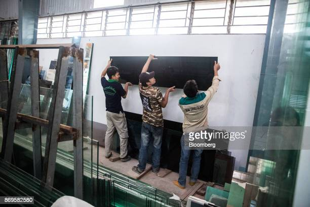 Workers hold a sheet of laminated glass at the Somvang Glass Factory on the outskirts of Vientiane Laos on Wednesday Nov 1 2017 Asia'ssmallest...