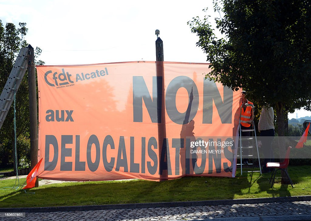 Workers hold a trade union banner reading : 'No to relocations' on October 8, 2013 in Orvault, western France, in front of a plant of French-US telecom-equipment maker Alcatel-Lucent, after the group announced the cut of 10,000 jobs worldwide to reduce fixed costs by 15 percent in two years, the company announced on October 8, 2013. The company said that 4,100 jobs would be cut in Europe, the Middle East and Africa by 2015, 3,800 in the Asia Pacific region, and 2,100 in North and South America. AFP PHOTO DAMIEN MEYER