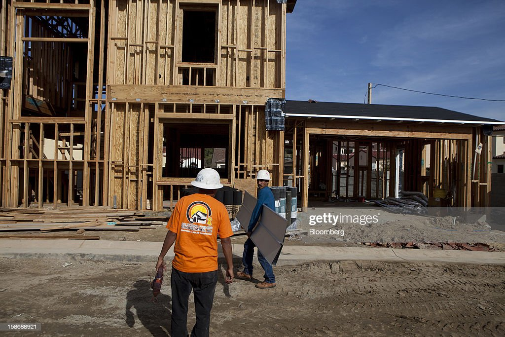 Workers hold materials and tools outside houses under construction at Davidson Communities LLC's Arista at The Crosby development in Rancho Santa Fe, California, U.S., on Friday, Dec. 21, 2012. New home sales climbed to a 380,000 annual rate in November, the most since April 2010, according to the median forecast of 60 economists surveyed by Bloomberg before Dec. 27 figures from the Commerce Department. Photographer: Sam Hodgson/Bloomberg via Getty Images