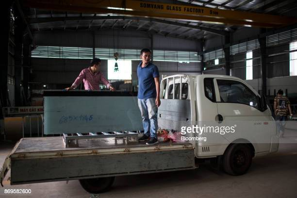 Workers hold sheets of glass as they stand on the back of a truck at the Somvang Glass Factory on the outskirts of Vientiane Laos on Wednesday Nov 1...