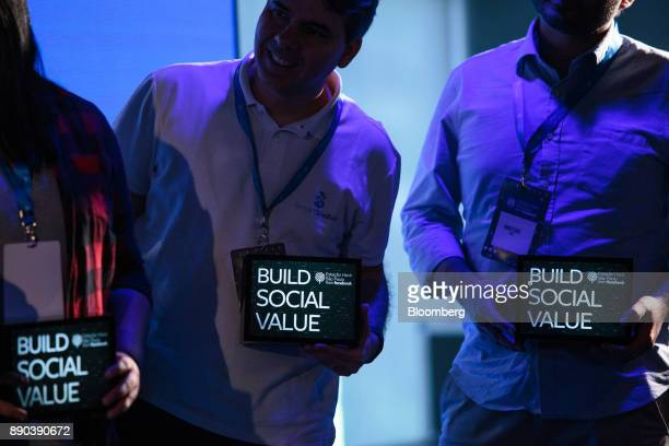 Workers hold signs that read 'Build Social Value' at the Facebook Inc Hack Station in Sao Paulo Brazil on Monday Dec 11 2017 The Facebook Hack...