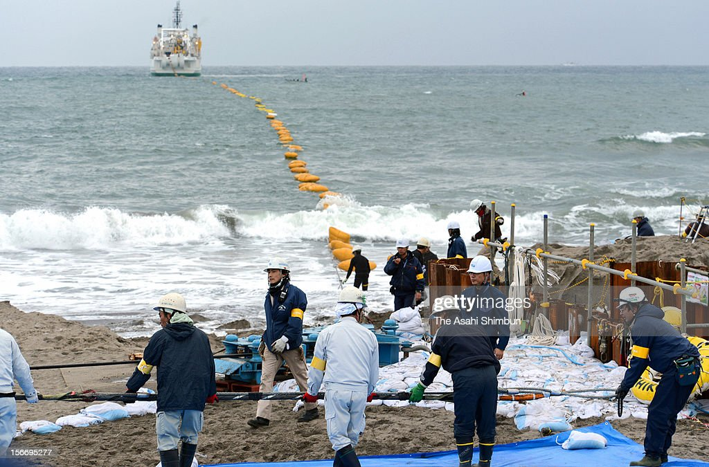 Workers hold the submarine cable to fix, ashore from the laying operation vessel on November 19, 2012 in Minamiboso, Chiba, Japan. The vessel sails toward Singapore by loying the 3.4 centimeter fiber optic submarine cable, the communications capacity between Japan and Southeast Asia will be reinforced 1.5 times as it is when the laying work will have been completed in 2013.