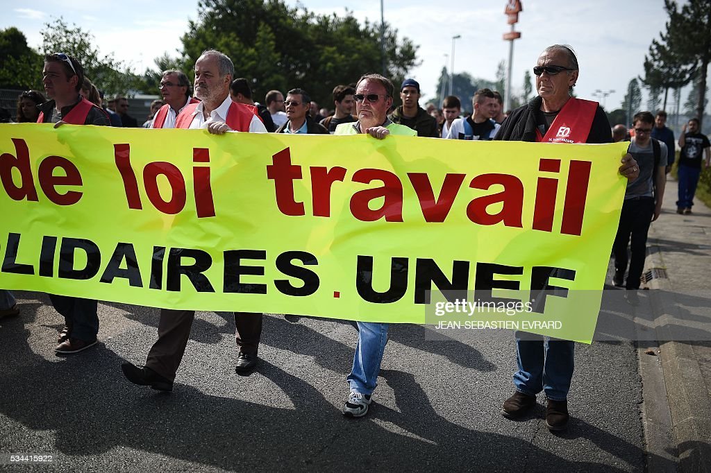 Workers hold up a banner that partially reads 'Labour law' in Saint-Nazaire, western France, as they protest against the government's planned labour law reforms on May 26, 2016. France's Socialist government has bypassed parliament and rammed through a labour reform bill that has sparked two months of massive street protests. / AFP / JEAN