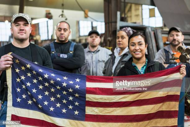 Workers holding American flag in factory