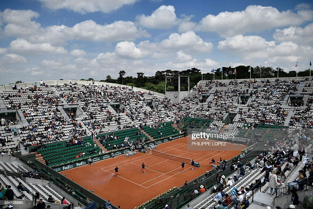 Workers hose the court at the Roland Garros 2016 French Tennis Open in Paris on May 25, 2016. / AFP / PHILIPPE