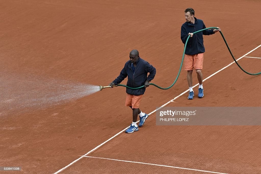 Workers hose the Philippe Chatrier court during the Roland Garros 2016 French Tennis Open in Paris on May 24, 2016. / AFP / PHILIPPE