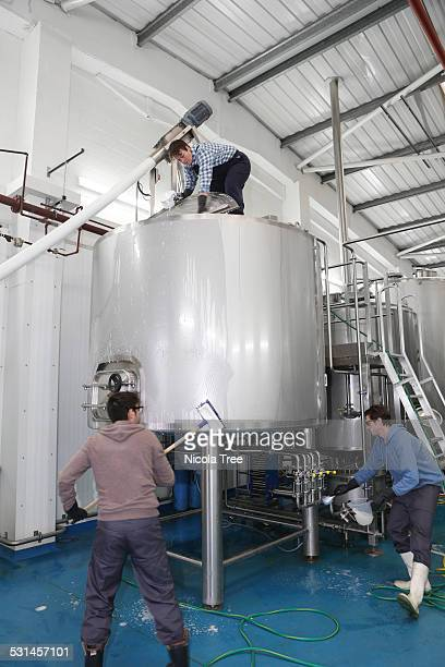 Workers in a micro brewery steralising the tanks