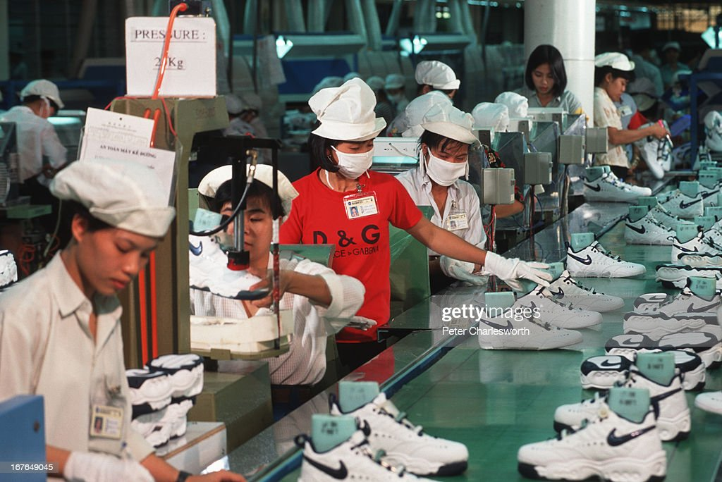Workers in a Nike factory near Ho Chi Minh City work at a production line conveyor belt putting together Nike sports shoes