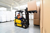 Workers in a warehouse - transport of goods with a forklift truck
