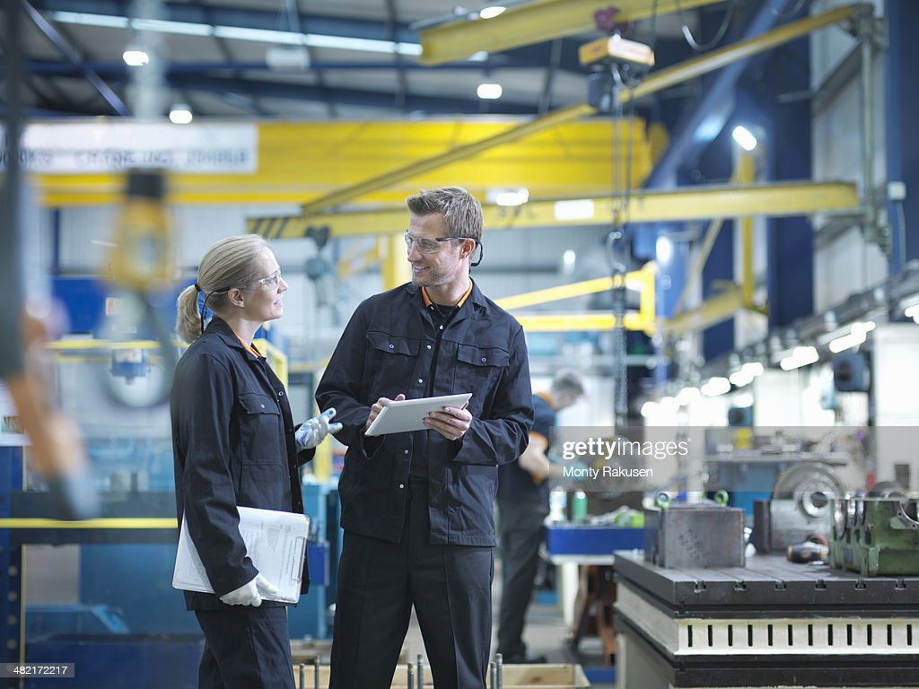 Workers in discussion in engineering factory
