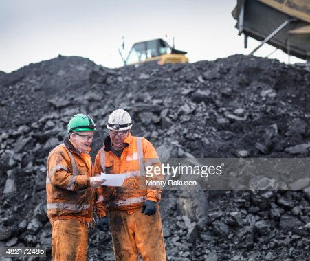 Workers in discussion in front of coal stocks in surface coal mine