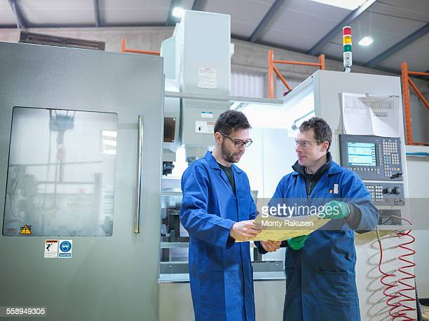 Workers in discussion next to CNC machine in plastics factory, portrait