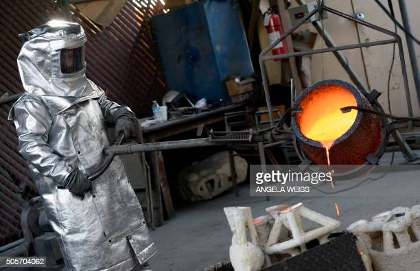Workers in fire suits pour molten bronze metal into molds during the casting of the Screen Actors Guild Award statuettes at the American Fine Arts...