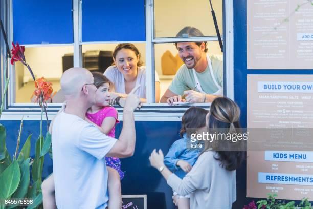 Workers in food truck helping customers