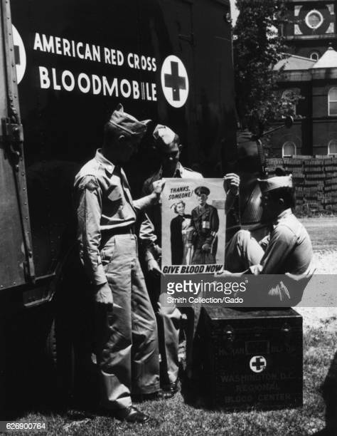 Workers in front of the American Red Cross bloodmobile holding signs that say Thanks Someone give blood now United States 1953 Courtesy National...