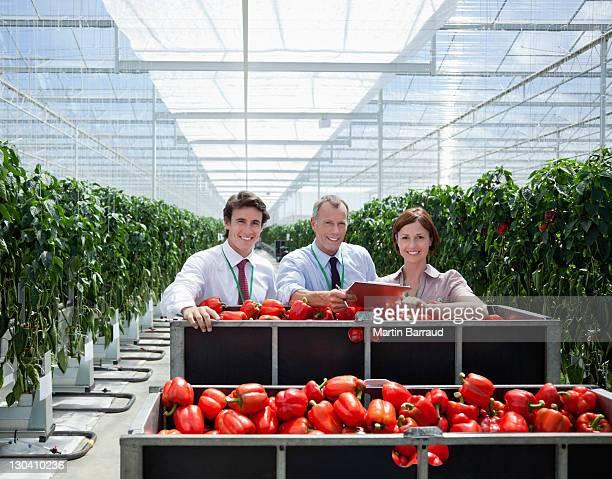 Travailleurs dans une serre debout avec des produits