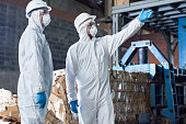 Portrait of two workers wearing biohazard suits standing in industrial warehouse of modern waste processing plant against recyclable cardboard in background