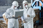 Portrait of two workers wearing biohazard suits using laptop  in industrial warehouse of modern waste processing plant against recyclable cardboard in background