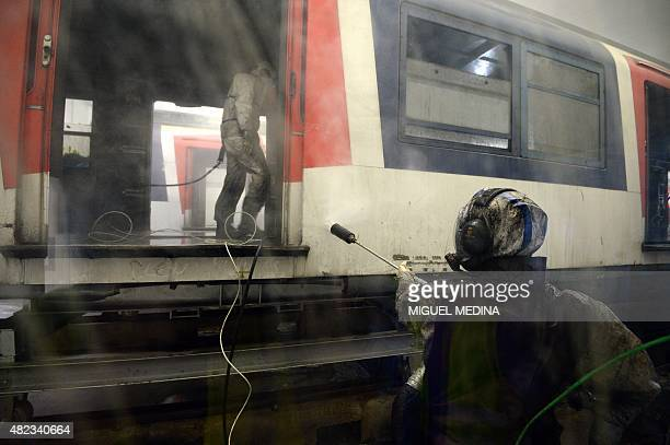 Workers in hermetic kevlar gear spray high pressure water to remove the asbestos from former carriages of the Paris RER regional express railway line...