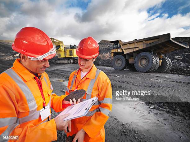 Workers In Mine Inspecting Coal