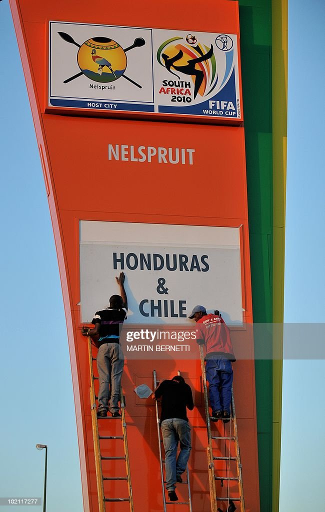Workers in Nelspruit put the finishing touches June 15, 2010 on a sign touting the 2010 World Cup Group H match between Chile and Honduras to take place June 16. AFP PHOTO / Martin BERNETTI