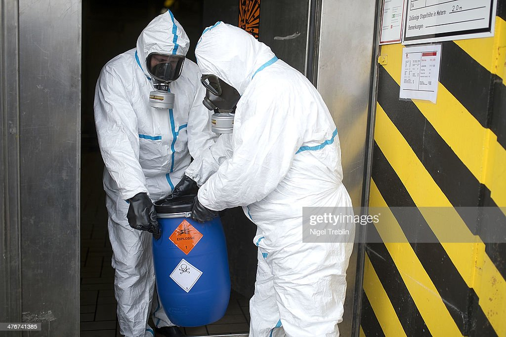 Workers in protective clothing carry a dummy grenade into a bunker during a press day at the GEKA facility on March 5 2014 in Munster Germany GEKA is...