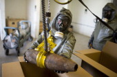 Workers in protective clothing unload a dummy grenade during a press day at the GEKA facility on March 5 2014 in Munster Germany GEKA is...