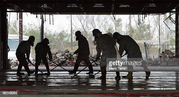 Workers in protective suits clean a school building in the heavily damaged Ninth Ward November 21 2005 in New Orleans Louisiana Most workers are...