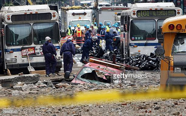 Workers in protective suits clean debris at the scene of a steam pipe explosion on Lexington Avenue July 19 2007 in New York City City officials said...