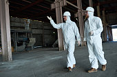 Full length portrait of two workers wearing biohazard suits walking in industrial warehouse of modern  plant,  copy space