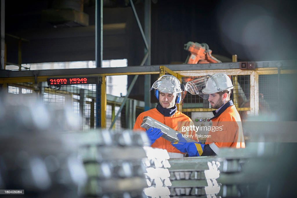 Workers in protective workwear inspecting aluminium ingot in foundry : Stock Photo