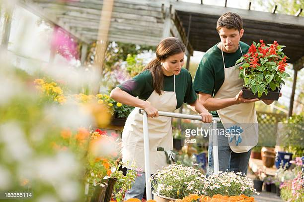 Workers in retail plant nursery with flowers