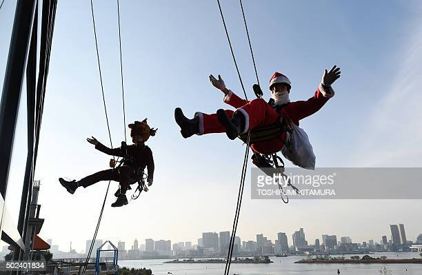 Workers in Santa Claus and reindeer costumes wave while cleaning windows outside a shopping mall along Tokyo's waterfront on December 24 2015 The...