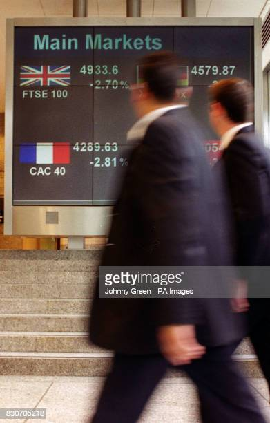 Workers in the London Stock Exchange in the City of London look at a board showing the FTSE 100 Index plunging below the 5000 mark for the first time...