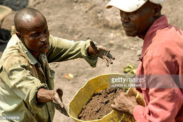 Workers in the Virunga National Park dig and scour the bed of a future canal on June 17 2014 in Matebe some 75 kms north of Goma Work on the...