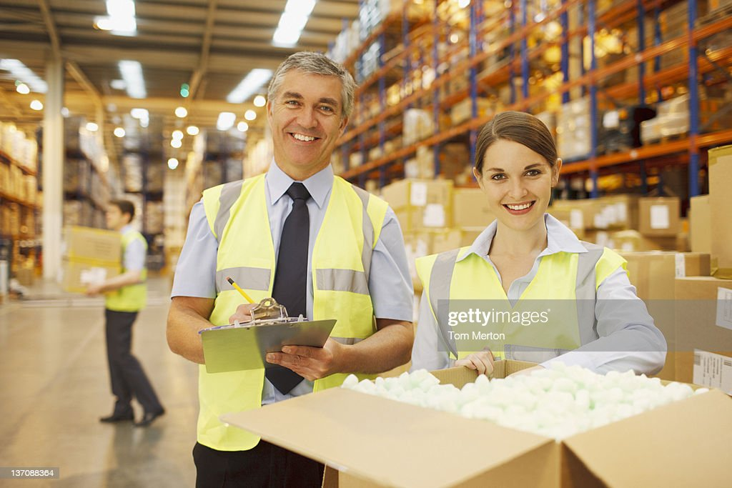 Workers in warehouse standing near box : Stock Photo