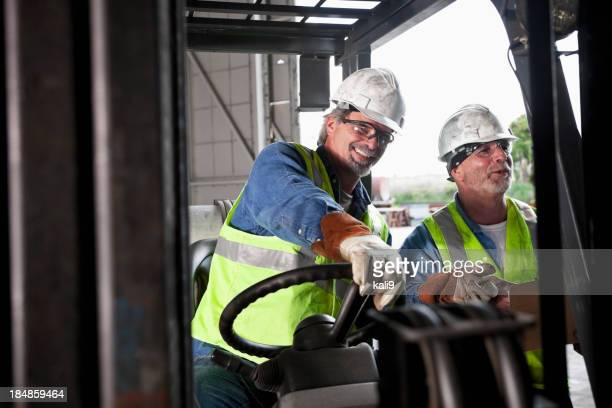 Workers in warehouse with forklift