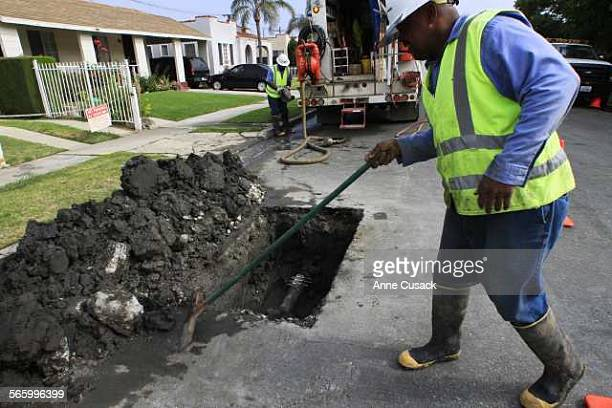 DWP workers including Brian Mitchell clean up after repairing a 6 inch water main that broke overnight in the 1700 block of Ridgely Drive in Los...