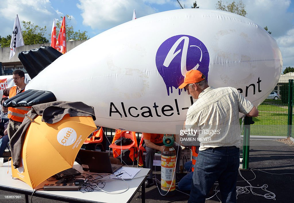 Workers inflate a balloon wearing the logo of Alcatel-Lucent, on October 8, 2013 in Orvault, western France, in front of a plant of French-US telecom-equipment maker, after the group announced the cut of 10,000 jobs worldwide to reduce fixed costs by 15 percent in two years, the company announced on October 8, 2013. The company said that 4,100 jobs would be cut in Europe, the Middle East and Africa by 2015, 3,800 in the Asia Pacific region, and 2,100 in North and South America.