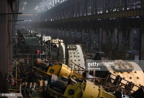 A workers inpects machinery as mills rotate in the dressing plant at the Lebedinsky GOK iron ore mining and processing plant operated by...